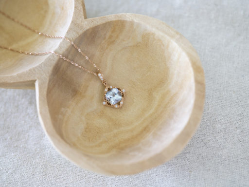 A gorgeous rose gold and aquamarine necklace laying in a wood bowl.