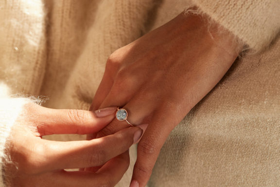 A woman places a beautiful aquamarine ring on her left hand.