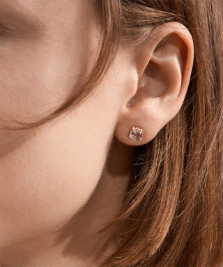 Close up of woman wearing morganite stud earrings.