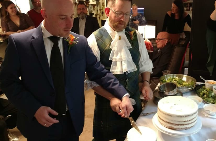 David and Lea cutting cake at their wedding.