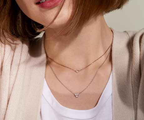 Woman wearing two small diamond pendant necklaces.