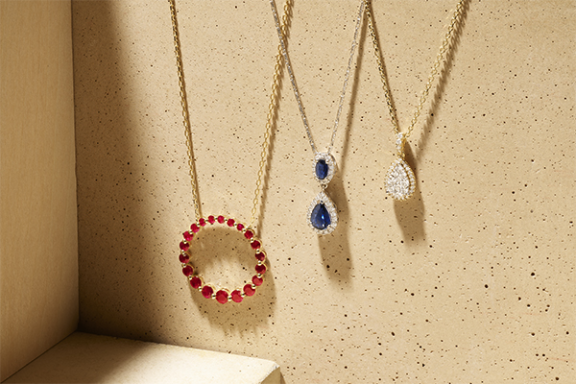 Ruby circle pendant, sapphire and diamond drop pendant, and diamond pear-shaped pendant.