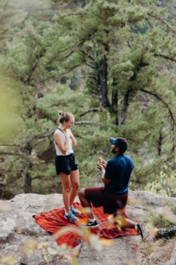 Man proposes to woman on blanket after hiking.