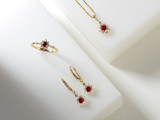 Yellow gold ruby and diamond cluster necklace, ring and dangle earrings on white background.