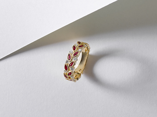 Yellow gold ruby and diamond ring with leaf-like detailing.