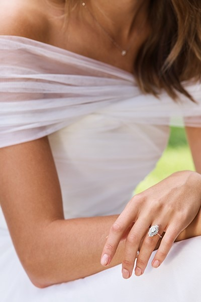 Close-up of bride wearing dress and engagement ring.