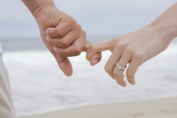 Holding hands with engagement ring on the beach.