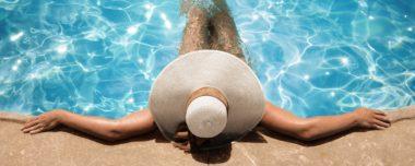 Woman laying in pool wearing hat.