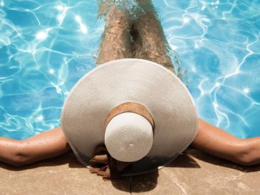 Woman laying in pool wearing hat.