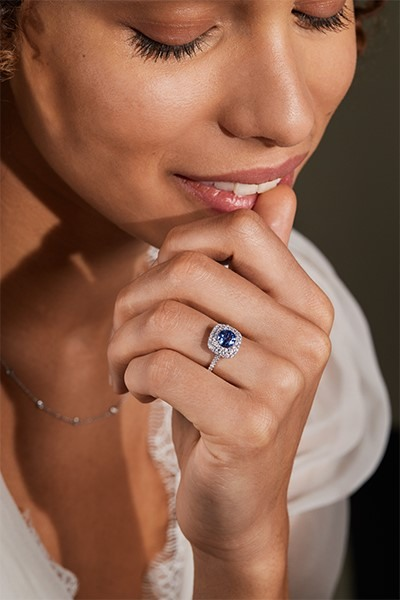 Close-up of a woman wearing a sapphire halo engagement ring.