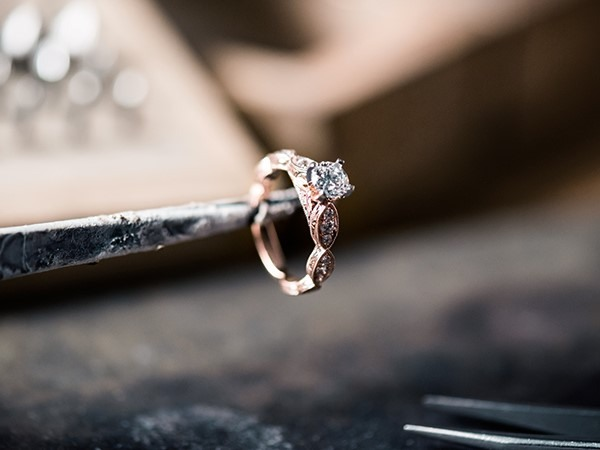 Holding an engagement ring with tweezers.