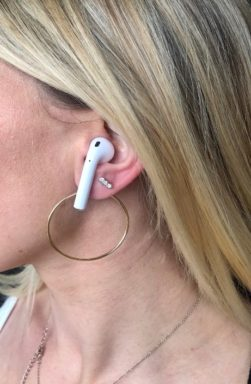 Woman wearing gold hoops with airPods.