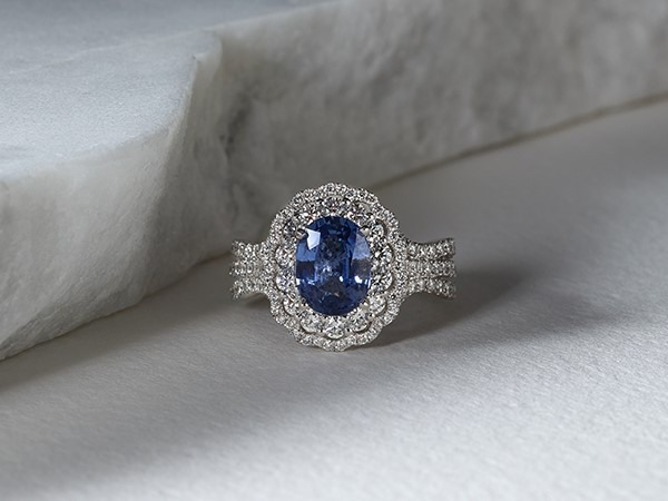 Oval blue sapphire and diamond halo engagement ring.