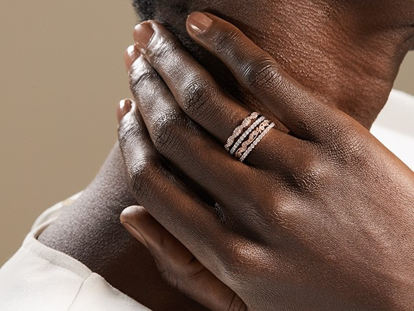 Woman wearing stacked wedding bands.