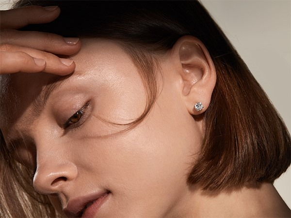 Woman wearing diamond studs.