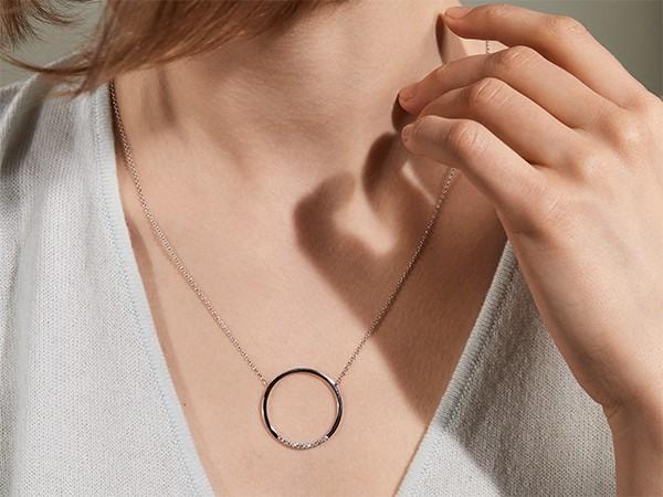 Woman wearing diamond circle necklace.