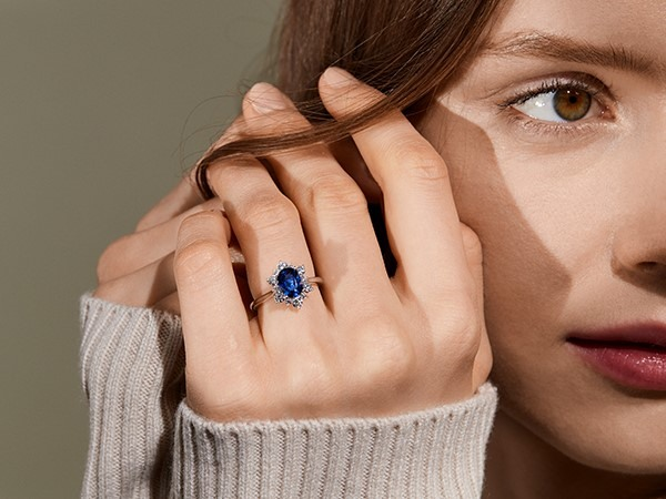 Woman wearing blue sapphire engagement ring.