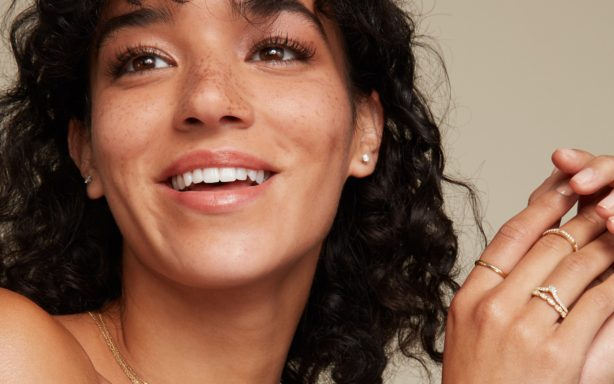 Woman smiling wearing Shane Co. jewelry.