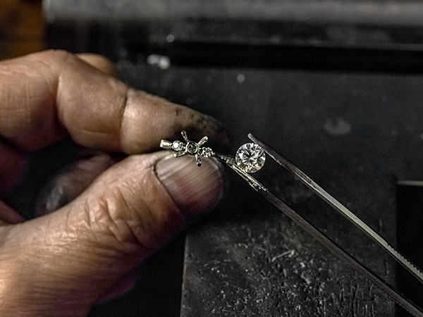Jeweler putting a diamond in an engagement ring setting.
