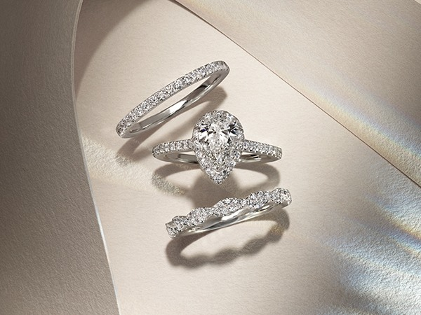 Pear-shaped engagement ring paired with two stackable wedding bands.