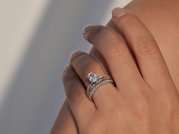 Woman wearing an oval engagement ring and two wedding bands.
