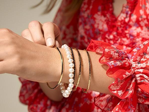 Woman wearing stacking bangle bracelets.
