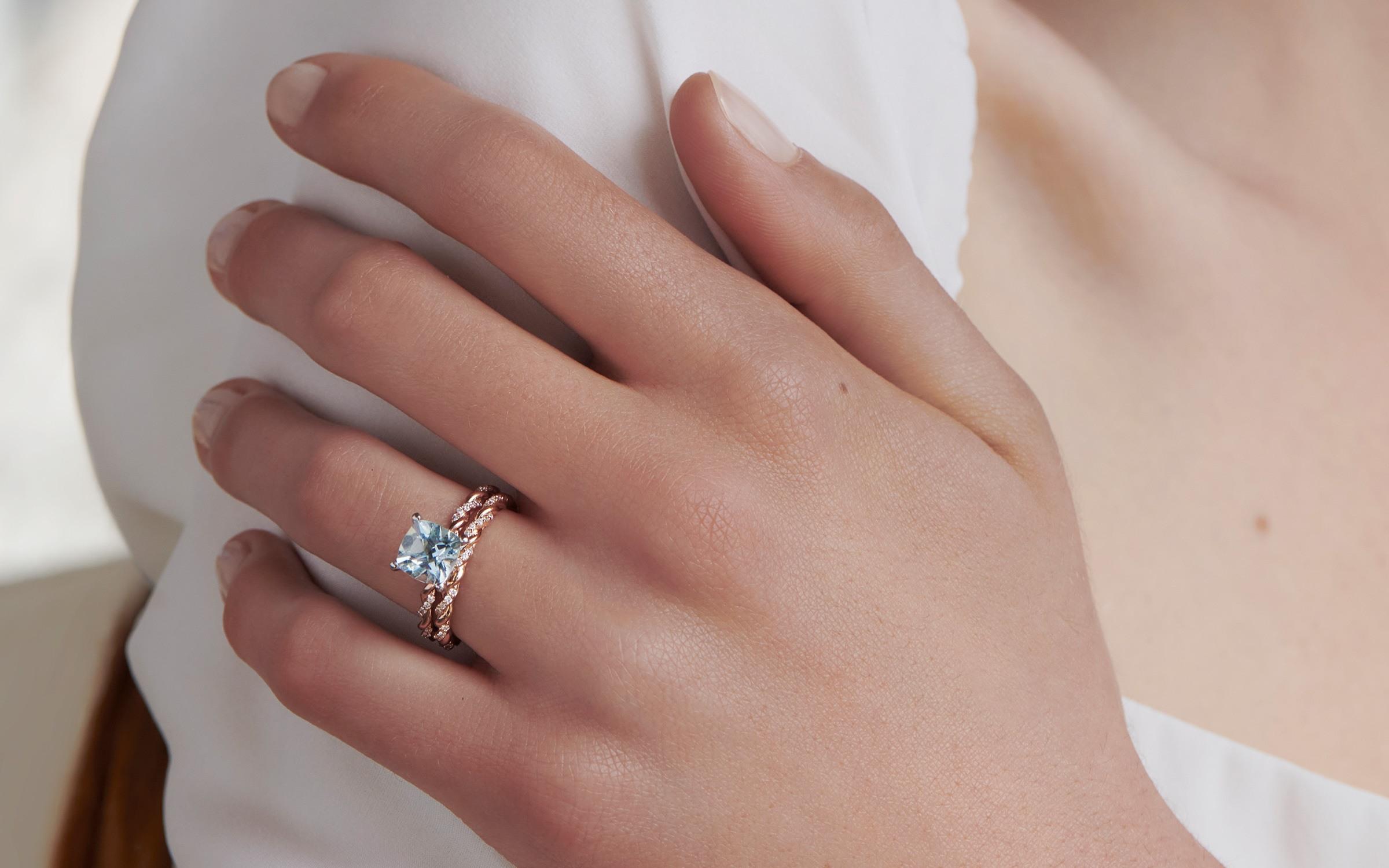 Woman wearing aquamarine engagement ring with rose gold wedding band.